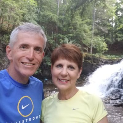 image of keith meyers and his wife with a waterfall in the background