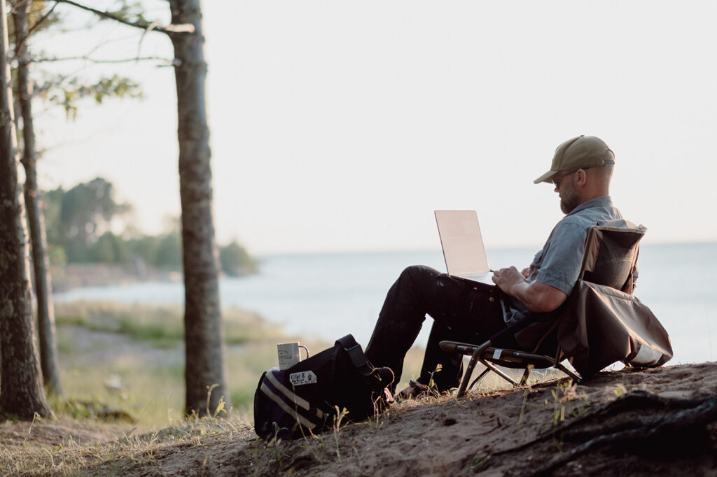 man wearing a ball cap sitting in a camp chair working on a laptop with the lake in the background